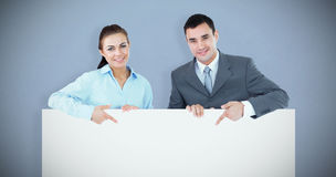 Composite image of business partners pointing at sign they are holding Stock Images