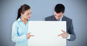 Composite image of business partners pointing at sign they are presenting Royalty Free Stock Photos