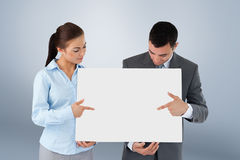 Composite image of business partners pointing at sign they are presenting Stock Image