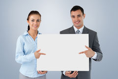 Composite image of business partners presenting sign together Royalty Free Stock Image