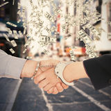 Composite image of business people in handcuffs shaking hands Stock Photo