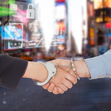 Composite image of business people in handcuffs shaking hands Royalty Free Stock Image
