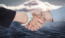 Composite image of business people in handcuffs shaking hands Stock Image