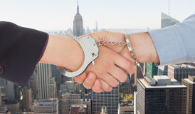 Composite image of business people in handcuffs shaking hands Stock Photos