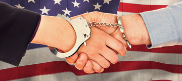 Composite image of business people in handcuffs shaking hands Stock Images