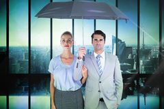 Composite image of business people holding a black umbrella Stock Photo