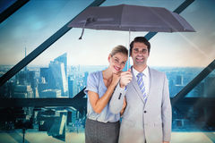 Composite image of business people holding a black umbrella Royalty Free Stock Photography