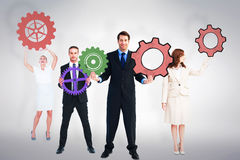Composite image of business people holding cogs Royalty Free Stock Photos