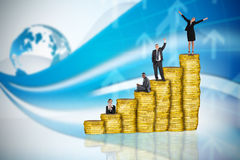 Composite image of business people on pile of coins Royalty Free Stock Images