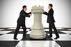 Composite image of business people pushing chess piece. Against white background with vignette Royalty Free Stock Photos