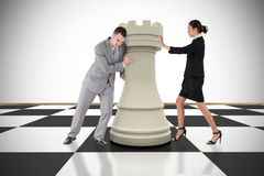 Composite image of business people pushing chess piece. Against white background with vignette Stock Image