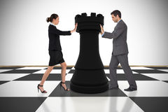 Composite image of business people pushing chess piece. Against white background with vignette Royalty Free Stock Image