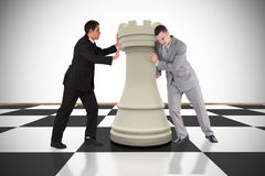 Composite image of business people pushing chess piece. Against white background with vignette Stock Images