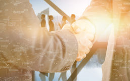 Composite image of business people shaking hands close up Royalty Free Stock Image