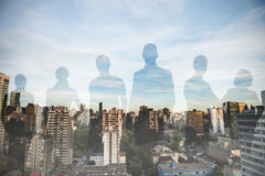 Composite image of business people standing against white background. Business people standing against white background against city against blue sky Royalty Free Stock Photos