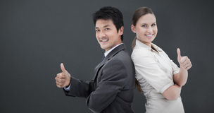 Composite image of business people standing back-to-back with the thumb up stock photography