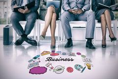 Composite image of business people waiting to be called into interview. Business people waiting to be called into interview against multi colored business text Stock Photo