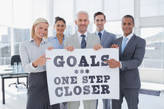 Composite image of business team holding large blank poster and pointing to it Royalty Free Stock Photo