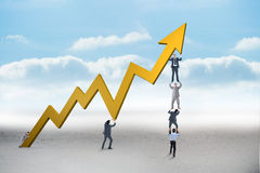 Composite image of business team holding up arrow Royalty Free Stock Photos