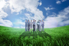 Composite image of business team looking at camera Stock Photo