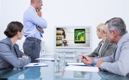 Composite image of business team looking at white screen Stock Image