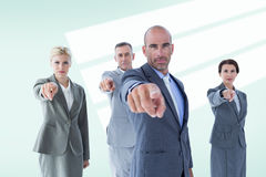 Composite image of business team pointing at the camera Royalty Free Stock Photography