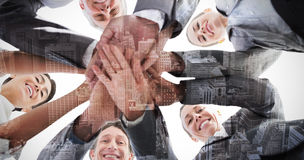 Composite image of business team standing hands together. Business team standing hands together against high angle view of city Royalty Free Stock Image