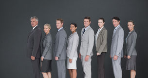 Composite image of business team standing in row and smiling at camera royalty free stock image