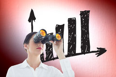 Composite image of business woman  looking through binoculars Stock Photo