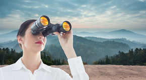 Composite image of business woman  looking through binoculars Royalty Free Stock Images