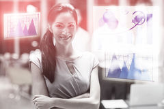 Composite image of business woman smiling against graph. Graph against happy businesswoman standing with arms crossed Stock Photos