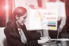 Composite image of business woman typing on laptop against colored graph. Graph against portrait of businesswoman working on laptop Stock Image