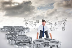 Composite image of businessman bending and lifting Stock Photo
