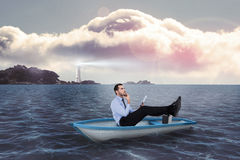 Composite image of businessman in boat with tablet pc Stock Photography