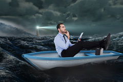 Composite image of businessman in boat with tablet pc Stock Images
