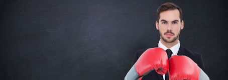 Composite image of businessman with boxing gloves. Businessman with boxing gloves against blackboard stock images