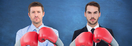 Composite image of businessman with boxing gloves. Businessman with boxing gloves against blue chalkboard royalty free stock image