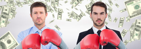 Composite image of businessman with boxing gloves. Businessman with boxing gloves against dollars falling stock photography