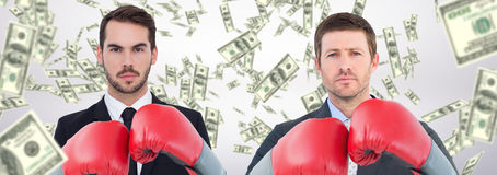 Composite image of businessman with boxing gloves. Businessman with boxing gloves against dollars falling royalty free stock photos