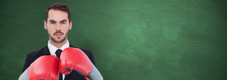 Composite image of businessman with boxing gloves. Businessman with boxing gloves against green chalkboard stock images