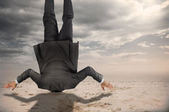 Composite image of businessman burying his head. Businessman burying his head against desert landscape stock photos