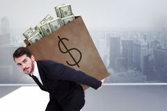 Composite image of businessman carrying bag of dollars Stock Images