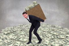 Composite image of businessman carrying bag of dollars Stock Photos
