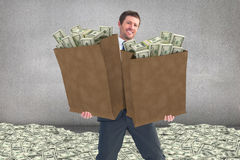 Composite image of businessman carrying bag of dollars Royalty Free Stock Image