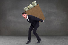 Composite image of businessman carrying something with his back and hands Stock Photo