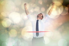 Composite image of businessman celebrating success with arms up Stock Photo