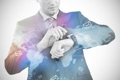 Composite image of businessman checking smart watch 3d. Businessman checking smart watch against futuristic technology interface 3d Stock Photos