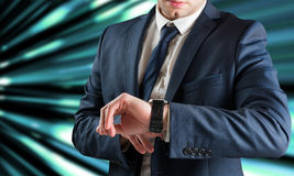 Composite image of businessman checking the time on watch Stock Image