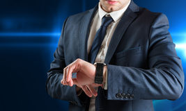 Composite image of businessman checking the time on watch Royalty Free Stock Image