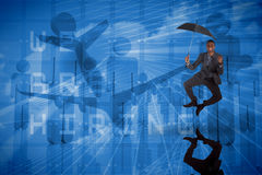 Composite image of businessman cheering and holding umbrella Stock Image